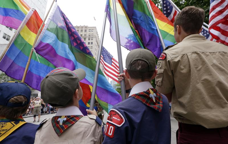 In this Sunday, June 28, 2015 file photo, Cub Scouts and Boy Scouts prepare to lead marchers while waving rainbow-colored flags at the 41st annual Pride Parade in Seattle, two days after the U.S. Supr