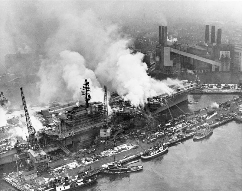 Smoke rises from the fire aboard the navy aircraft carrier USS Constellation at the Brooklyn Navy Yard on the East River in New York, Dec. 19, 1960.