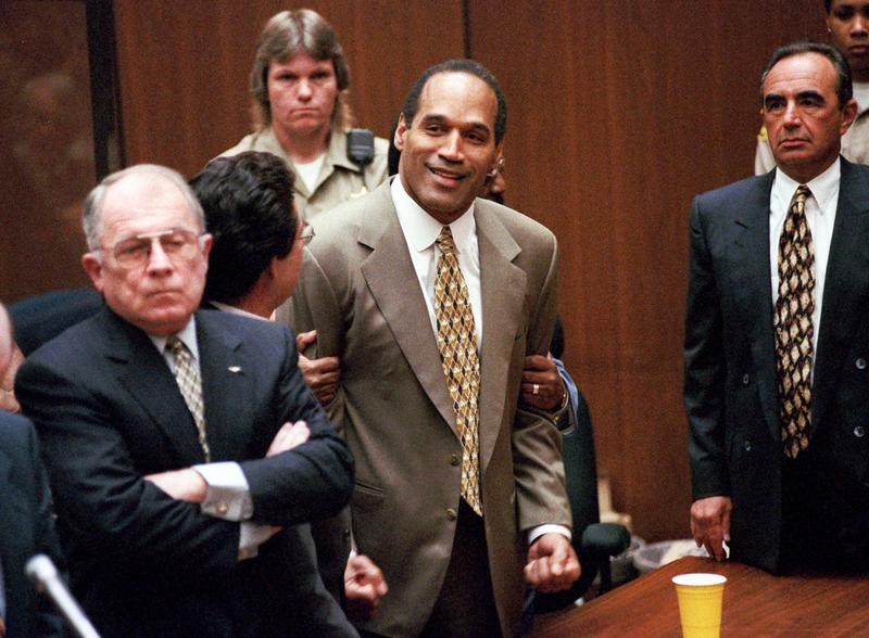 In this Oct. 3, 1995 file photo, O.J. Simpson, center, clenches his fists in victory after the jury said he was not guilty at his murder trial.