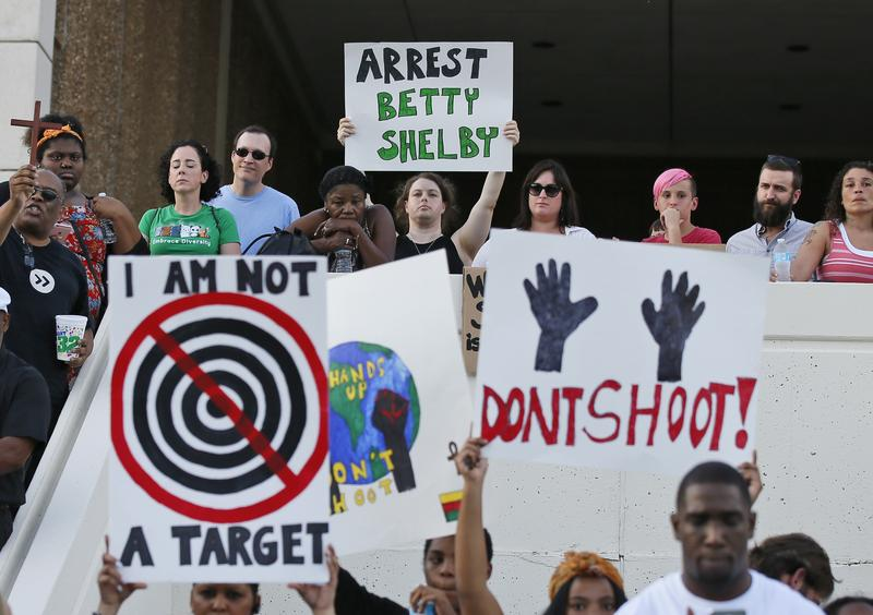 """People hold signs at a """"protest for justice"""" over Friday's shooting death of Terence Crutcher, sponsored by We the People Oklahoma, in Tulsa, Okla., Tuesday, Sept. 20, 2016."""