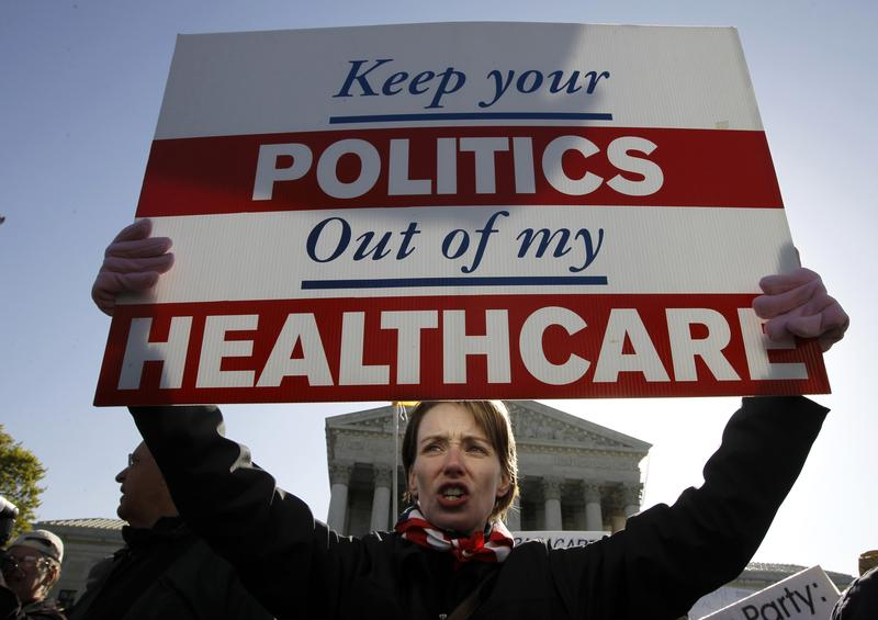 In this Tuesday, March 27, 2012 file photo, Amy Brighton from Medina, Ohio, who opposes health care reform, holds a sign in front of the Supreme Court.