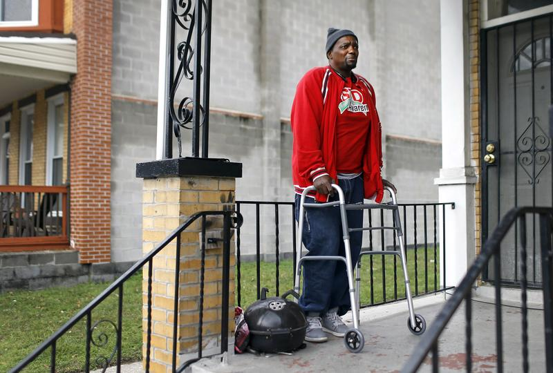 In this Dec. 30, 2015 photo, Clifton Gerald, a survivor of two instances of gun violence, stands on his front porch in Baltimore.