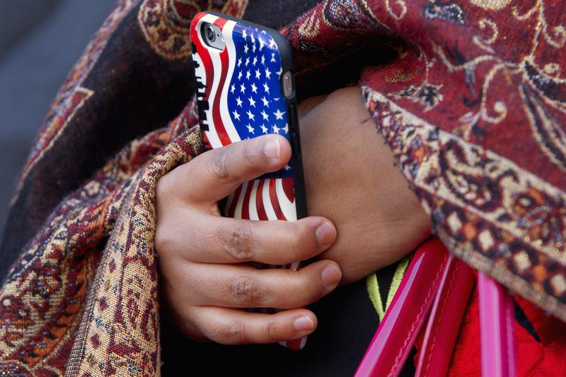 A Muslim woman holds a cell phone with a U.S. flag cover as Rep. Don Beyer, D-Va. speaks after attending Friday prayers at Dar al-Hijrah Mosque in Falls Church, Va., Friday, Dec. 4, 2015.