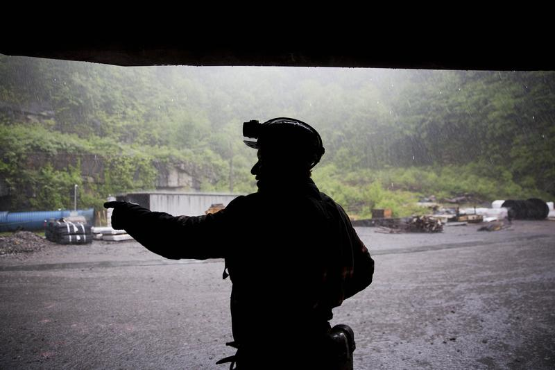 In this Thursday, May 12, 2016 photo, coal miner Scott Tiller takes shelter from the rain after coming out of an underground mine at the end of a shift in Welch, W.Va.