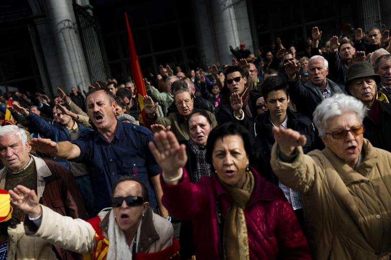 Far-right wing supporters rise their right arm saluting the fascist anthem as they remember former Spanish Dictator Francisco Franco on the 39th anniversary of his death, in Madrid. Nov. 23, 2014