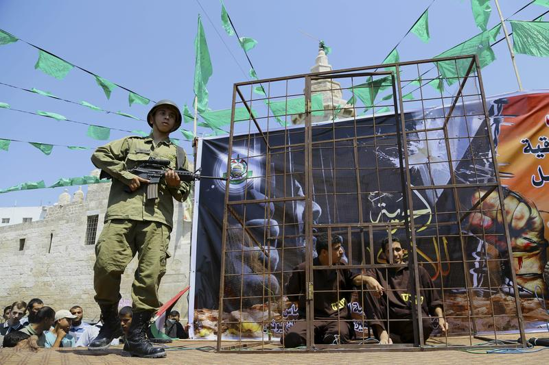 05/23/14: A Palestinian from the military wing of Hamas mimics an Israeli solder while standing by a representation of a prison cell during a rally to support Palestinian prisoners on hunger strike.