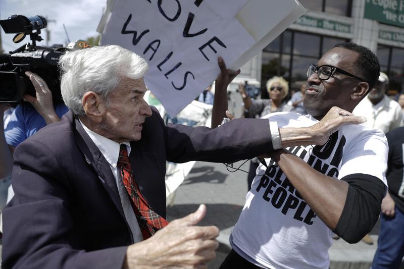 Jerry Lambert, left, a Trump supporter, and Asa Khalif, a Black Lives Matter activist, scuffle, after Khalif took Lambert's sign during a protest. Sept. 2, 2016