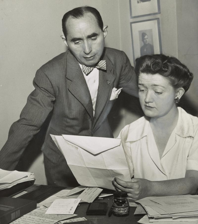 New York City theatrical agent Audrey Wood reading correspondence as her husband and business partner William Liebling looks on.