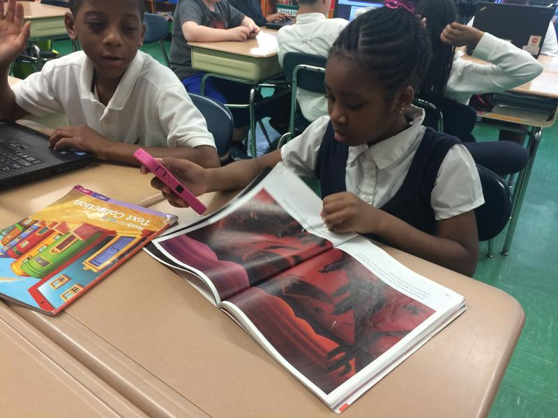 Amy, a fourth-grader at P.S. 129, references reading material before participating in a class Q&A on her cellphone.