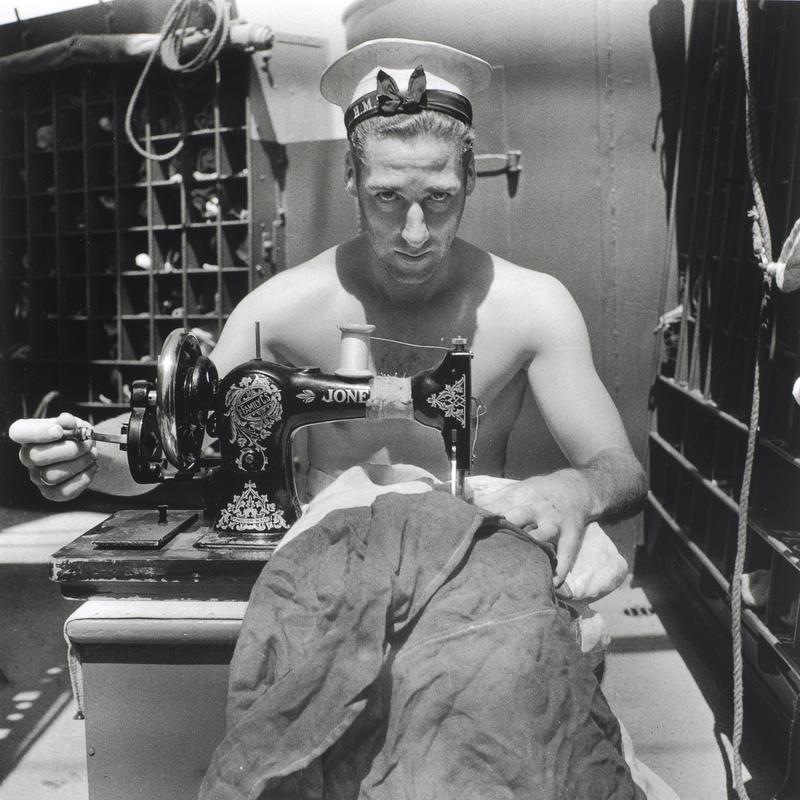 A Royal Navy sailor on board HMS Alcantara uses a portable sewing machine to repair a signal flag during a voyage to Sierra Leone, March 1942