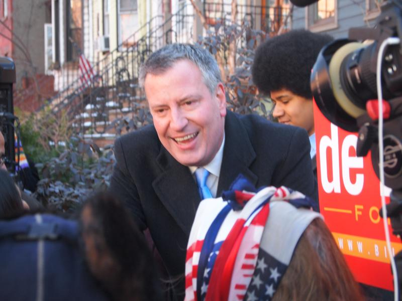 Bill De Blasio reaches out to supporters as his son Dante stands nearby