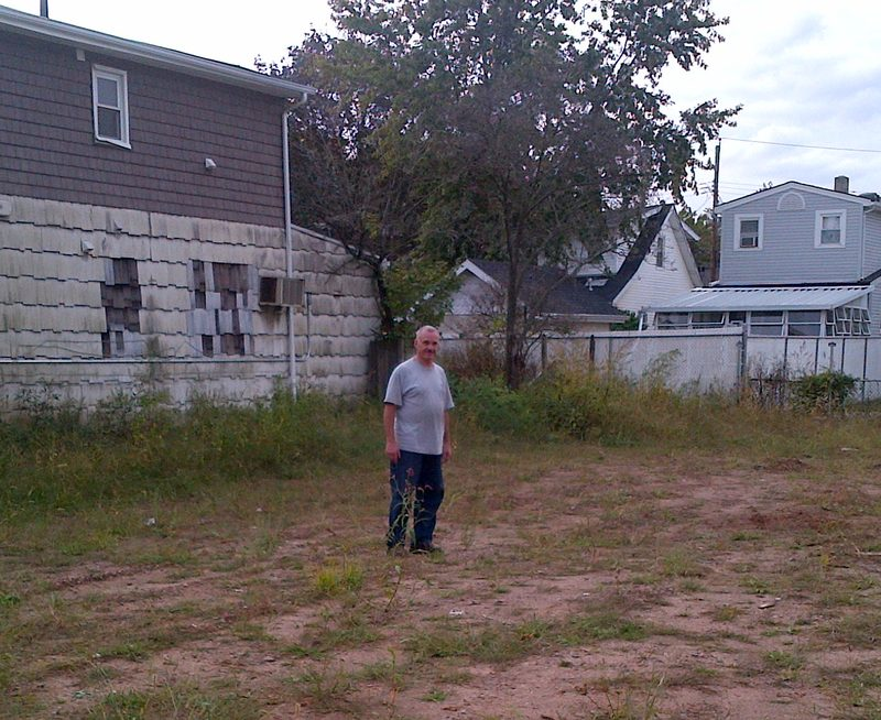 Bill Owens in front of the vacant lot in Midland Beach, Staten Island, where his house once stood.