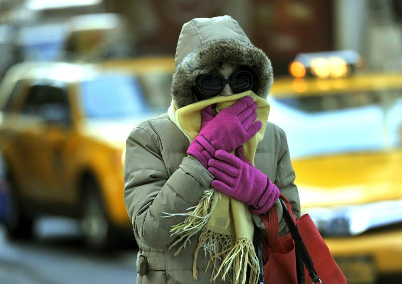 A woman braces from the cold during the morning commute in New York City as temperatures dropped into the lower 30s. November 2013