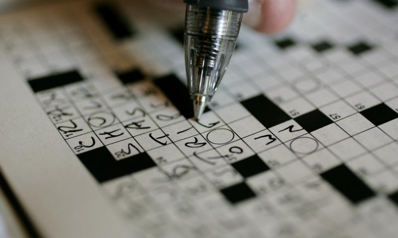 A puzzle fan works on a New York Times crossword puzzle