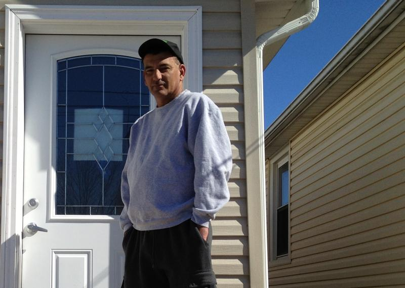 Stephen Drimalas stands in front of his renovated home in Ocean Breeze, Staten Island, which was hit hard by Sandy.