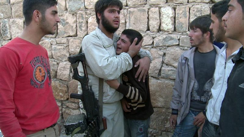 A young boy is consoled after his grandparents appear to have been killed in a government strike on the Sunni village of Al Barra.