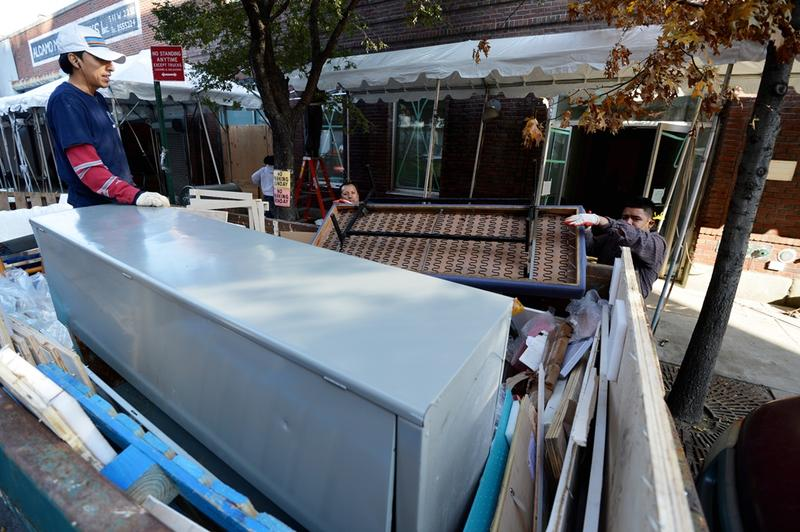 Men remove damaged furniture from a building housing several art galleries November 12, 2012 in the Chelsea section of New York as the city recovers from the effects of Hurricane Sandy.