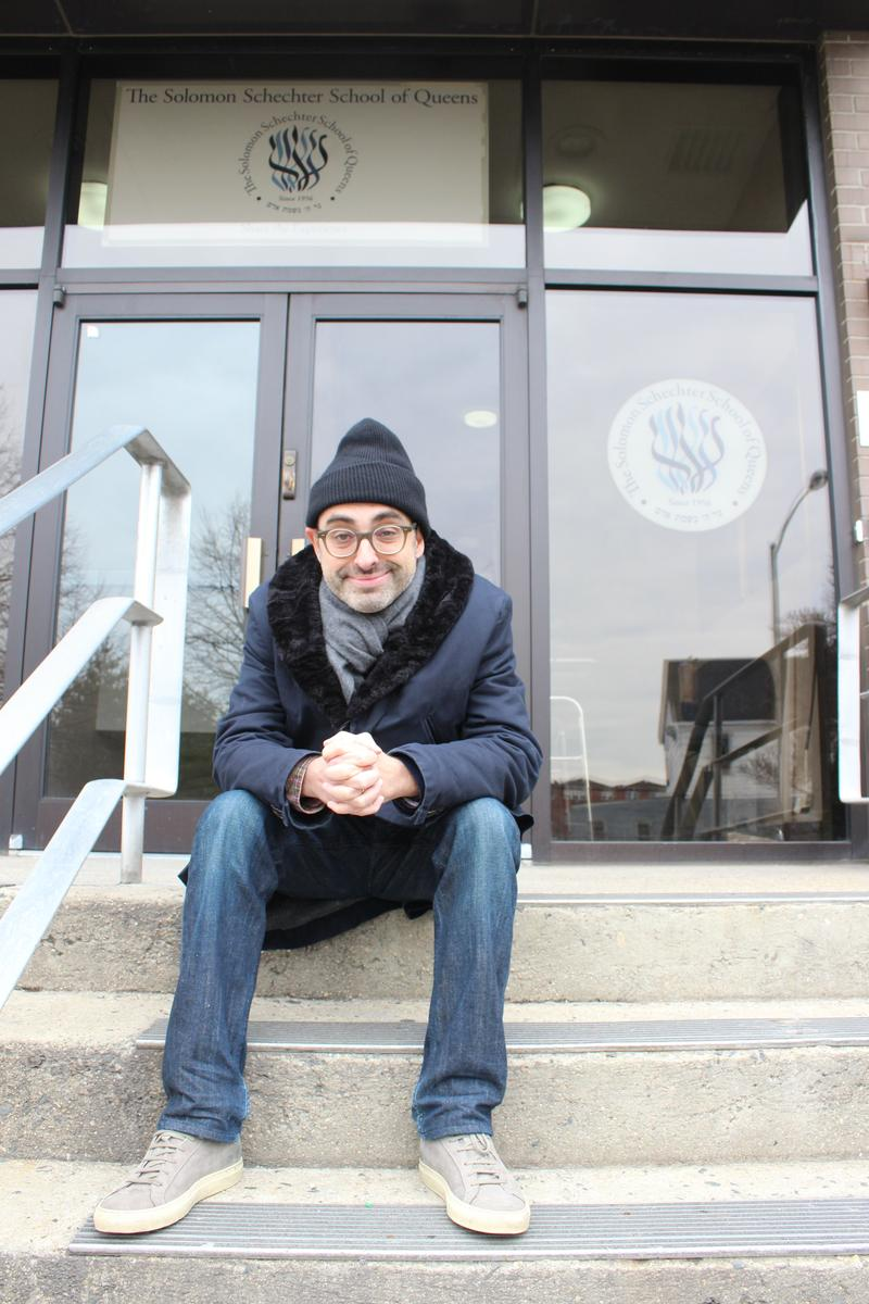 Writer Gary Shteyngart sits on the steps of his old school, the Solomon Schechter School of Queens.