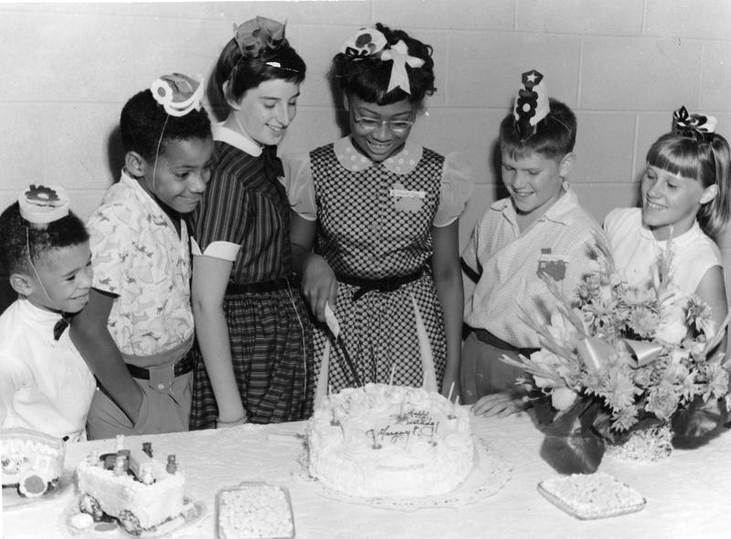 Portrait of a group of children at birthday party where one is about to cut the cake, upon which is written 'Happy Birthday Margaret,' 1959.