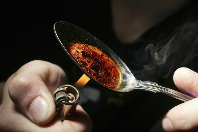 Re-enactment of heroin user burning heroin on spoon. Heroin is a white brownish powder that can be smoked, sniffed or dissolved in water and injected.