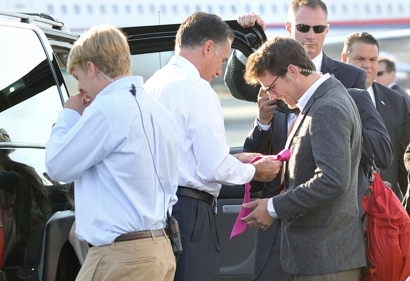US Republican presidential candidate Mitt Romney hands trip director Charlie Pearce a tie on the tarmac of Love Field airport in Dallas, Texas on September 19, 2012.