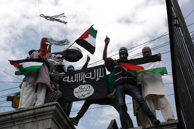 Kashmiri protesters hold up a flag of the Islamic State of Iraq and the Levant (ISIL), during a protest against Israeli military operations in Gaza, on July 18, 2014 in Srinagar, India.