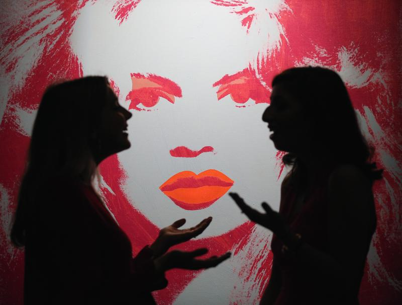 Employees pose next to a painting by Andy Warhol at Sotheby's on October 10, 2014 in London, England. Warhol was a past winner of the Scholastic Art & Writing Awards.