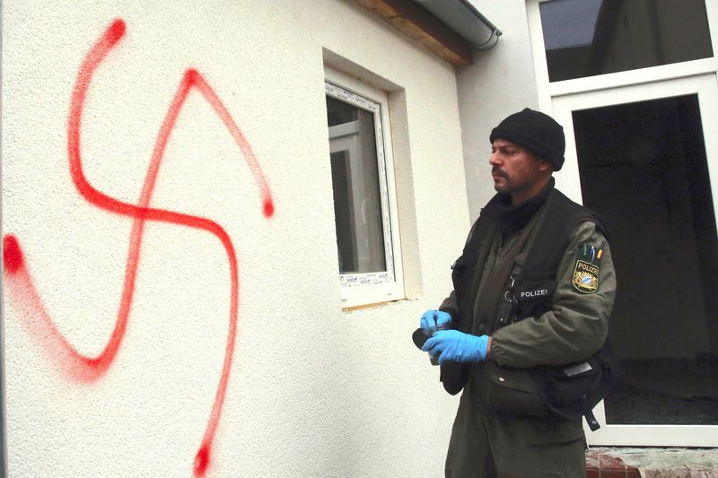 A police investigator stands in front of a house for asylum seekers and refugees that was damaged in an arson and vandalism attack in Vorra, in southern Germany near Nuremberg on December 12, 2014.