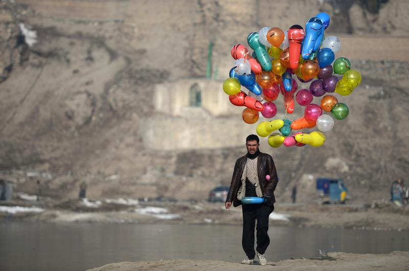 An Afghan man carries balloons for sale as he walks at Shuhada Lake in Kabul on February 10, 2014. Despite economic improvement in the last decade, Afghanistan is still extremely poor.