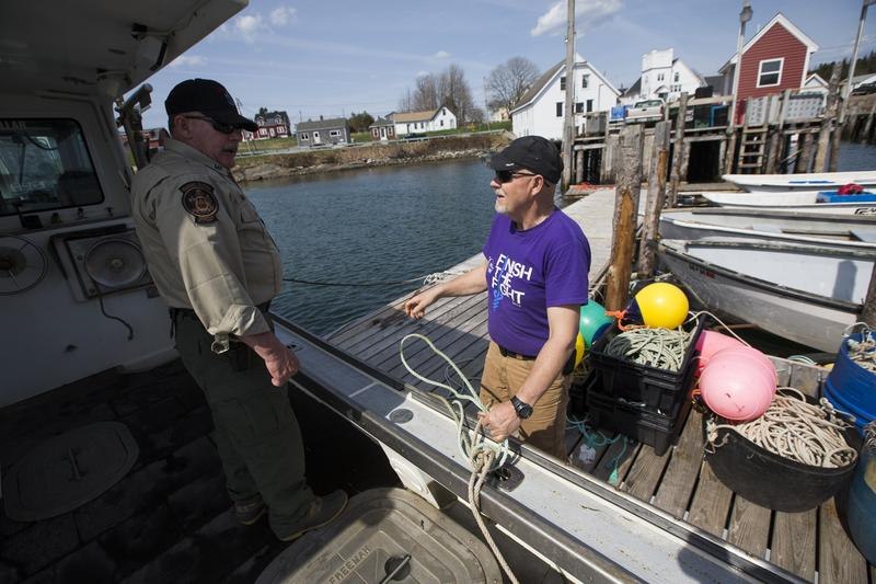 Maine Marine Patrol specialist Mark Murry speaks with lobsterman Brian Cates, right, in Cutler, Maine, May 7, 2015.