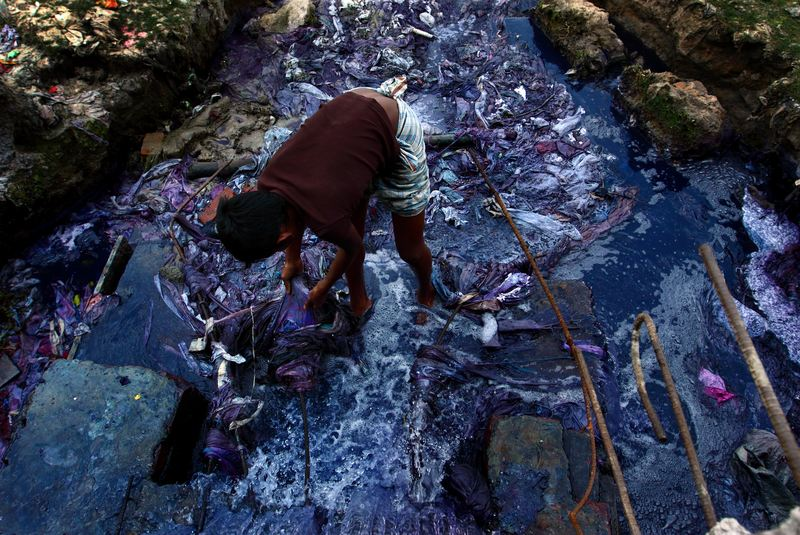 GAZIPUR, BANGLADESH - 2011/02/25: Every day, 9-year-old Jashim collects pieces of cloth from the liquid waste of the dyeing industries.