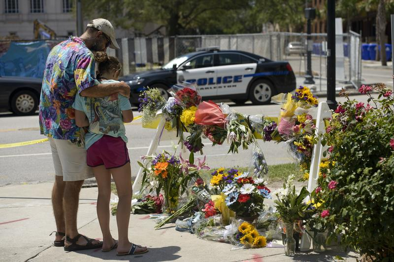 People visit a makeshift memorial near the Emanuel AME Church June 18, 2015 in Charleston, South Carolina, after a mass shooting at the Church on the evening of June 17, 2015.