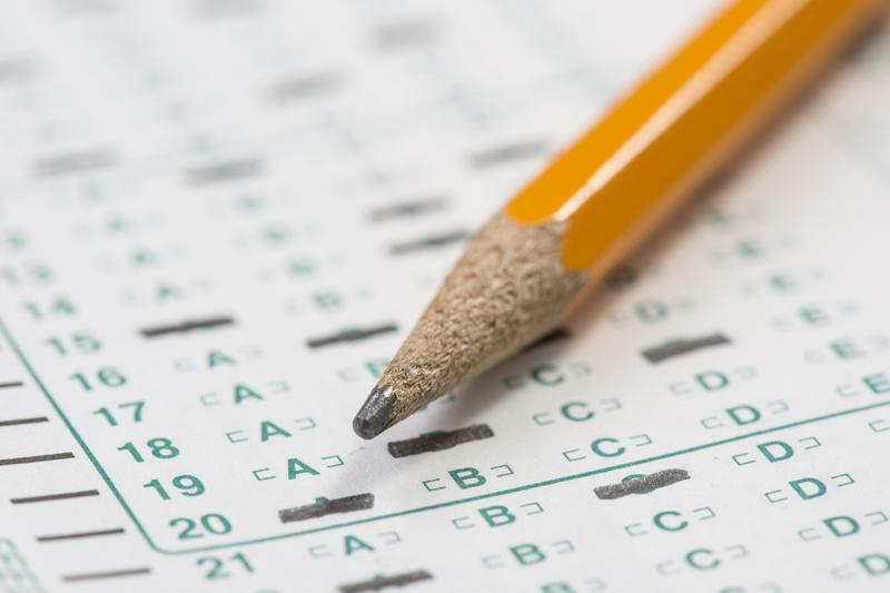 Standardized test answer sheet and pencil.
