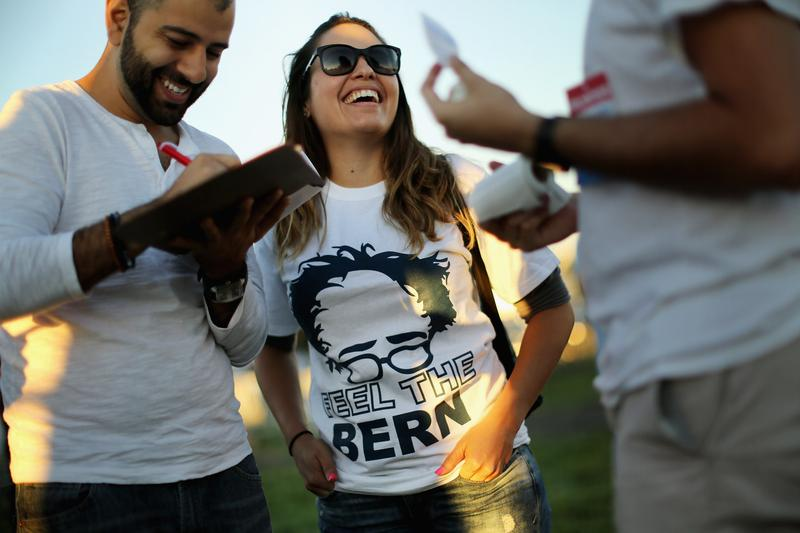 Supporters sign a petition to get Democratic presidential candidate Sen. Bernie Sanders (I-VT) on the ballot in Virginia during a campaign rally at the Prince William County Fairground Sept. 14, 2015.