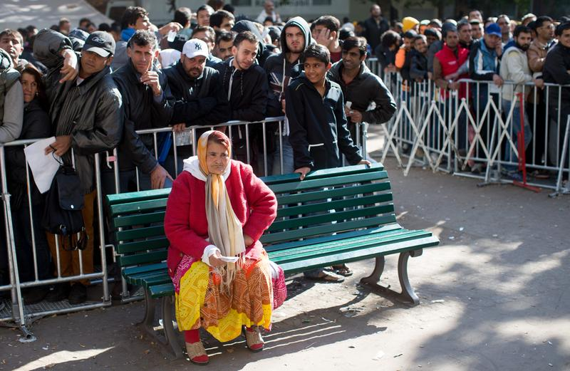 A refugee sits while waiting in line in Berlin.