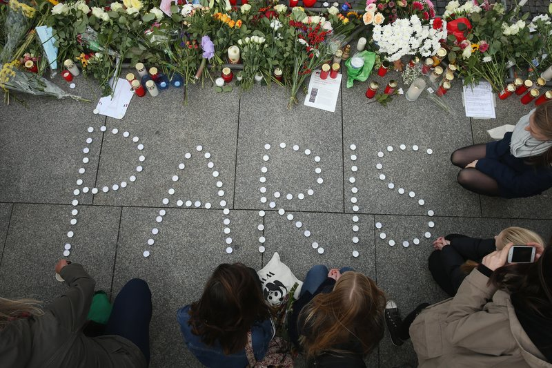 People finish arranging candles into the word 'Paris' next to flowers and messages left at the gate of the French Embassy following the recent terror attacks in Paris on November 14, 2015 in Berlin.