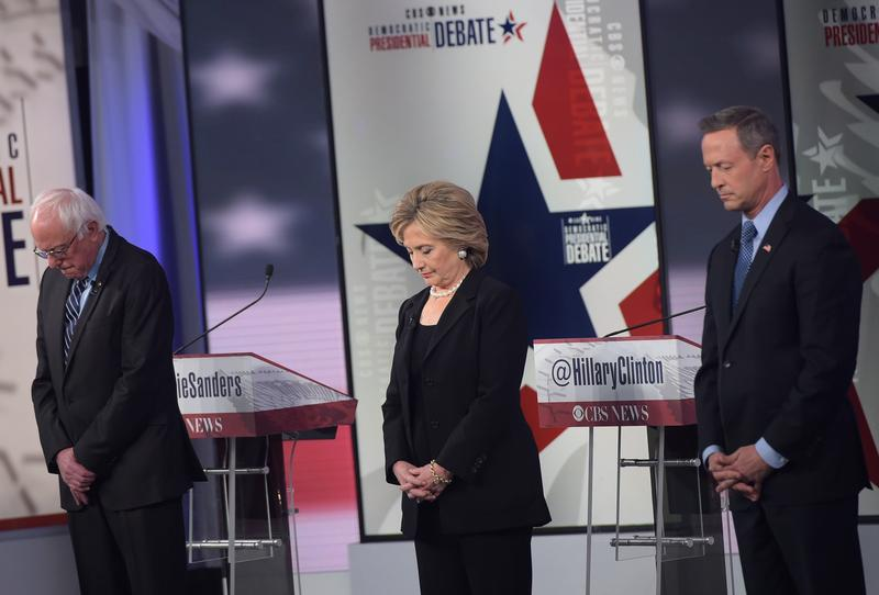 Democratic candidates Bernie Sanders, Hillary Clinton, and Martin O'Malley pause for a moment of silence for the victims of the Paris terrorists attacks before the start of the 2nd Democratic debate.