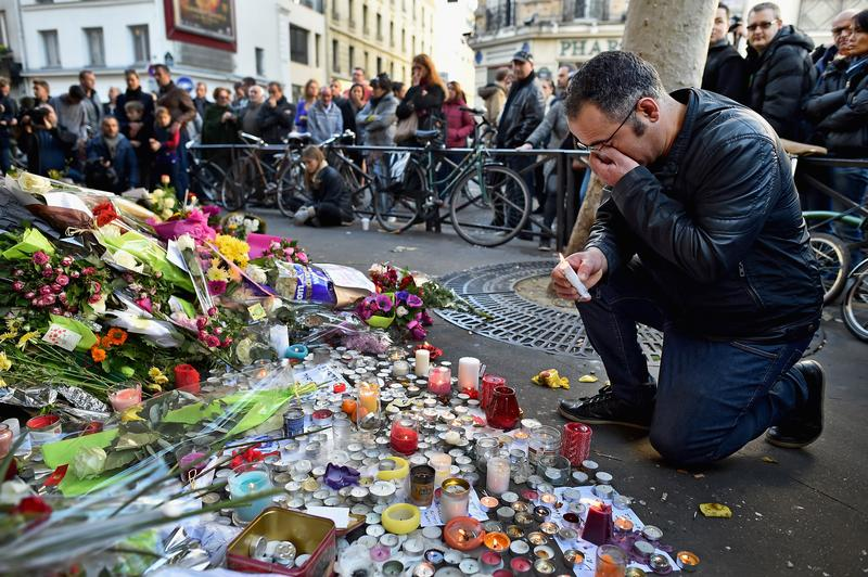 Members of the public gather to lay flowers and light candles at La Belle Equipe restaraunt on Rue de Charonne following Fridays terrorist attack on November 15, 2015 in Paris, France.