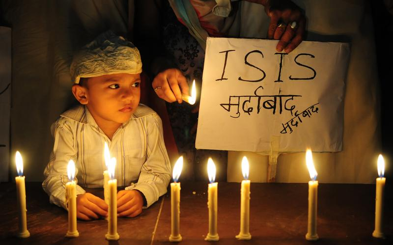 A Muslim kid holds placard with slogan against the ISIS during a candle light vigil to express solidarity with the victims of Paris terror attacks on November 15, 2015 in Bhopal, India.