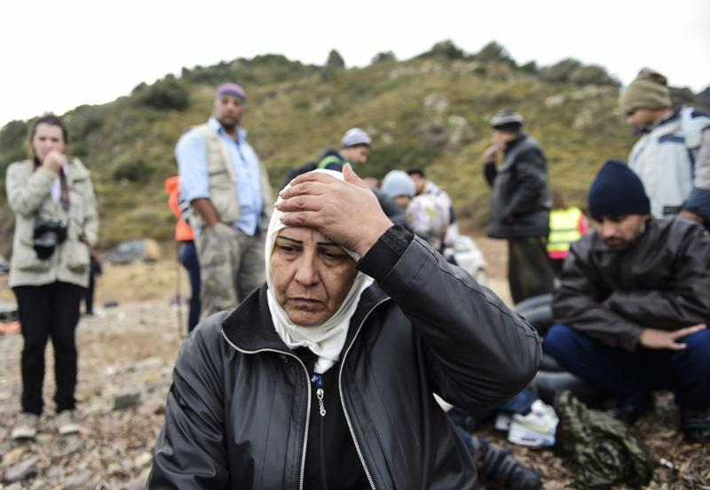 Syrian refugees wait just after their arrival on the Greek island of Lesbos after crossing the Aegean Sea from Turkey on November 16, 2015.