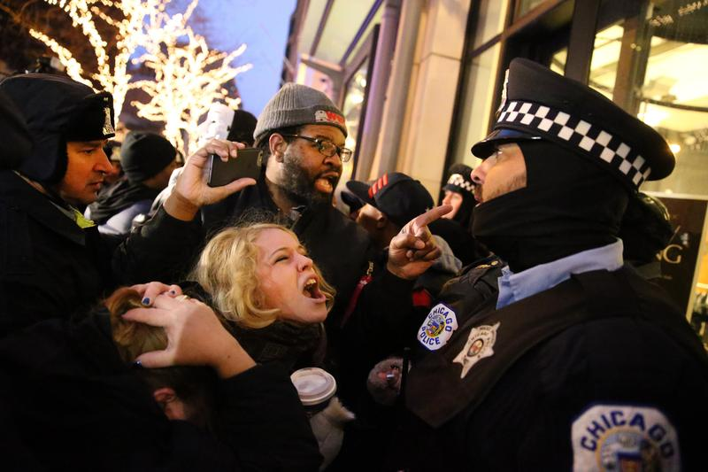 People scream at cops as they protest the shooting death of Laquan McDonald during a clash with Chicago police officers outside of a Banana Republic store on Michigan Avenue on Friday, Nov. 27, 2015.