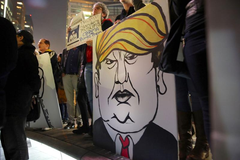 A protester holds a caricature of conservative presidential candidate Donald Trump during a demonstration against racism and Trump's recent remarks concerning Muslims on December 10, 2015.