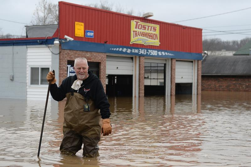 A man in Fenton, Missouri, wades through the flooding to inspect his business.