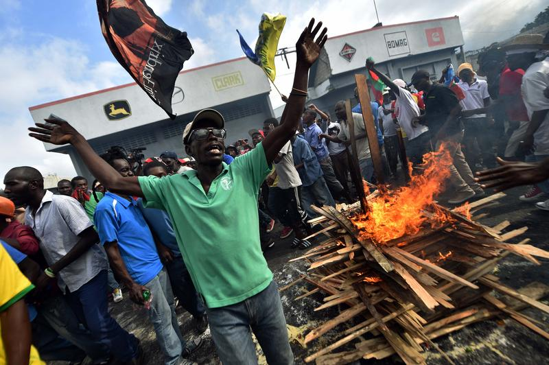 Protesters run around the fire while perform a voodoo ceremony prior a march in Port-au-Prince, on January 24, 2016 to demand the resignation of Haitian President, Michel Martelly.