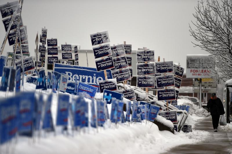 An elderly man walks past campaign signs of US Democratic presidential candidates Hillary Clinton and Bernie Sanders in Manchester, New Hampshire, on February 5, 2016.