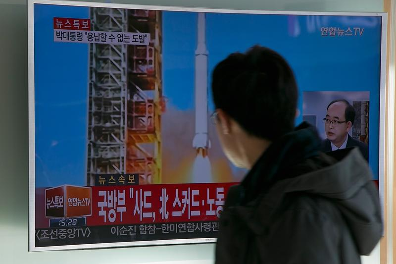 People watch a television screen showing a breaking news on North Korea's long-range rocket launch at Seoul Station on February 7, 2016 in Seoul, South Korea.