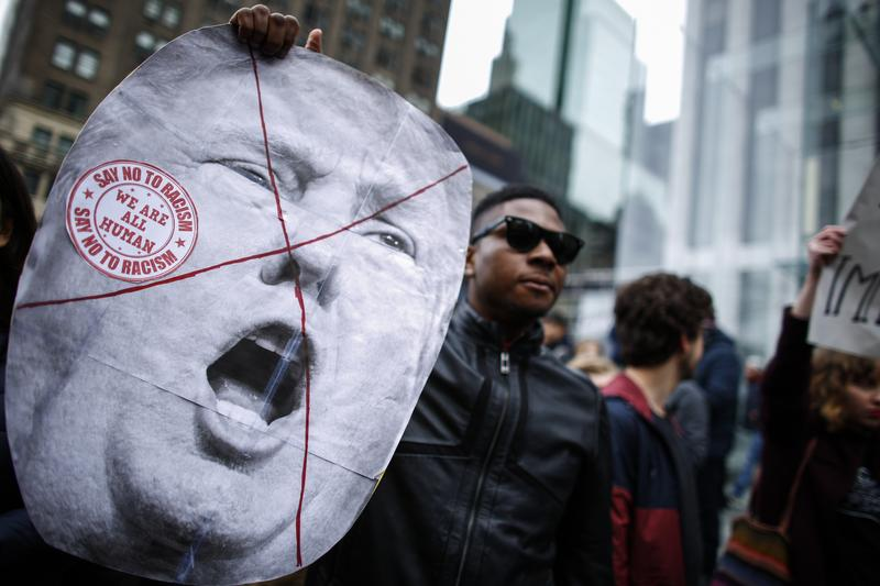 A man holds a sign as he takes part in a protest against Republican presidential front-runner Donald Trump in New York on March 19,2016.