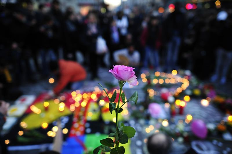 A local holds a rose while others ignite Flowers and candles at Beursplein square following todays attack on March 22, 2016 in Brussels, Belgium.