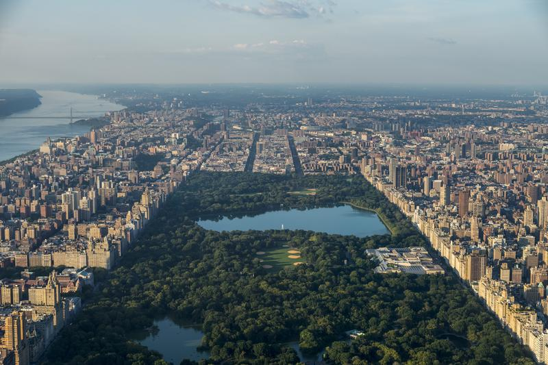Aerial over Central Park looking uptown in Manhattan in NYC, Jacqueline Kennedy reservoir, George Washington Bridge, Hudson River, and buildings surrounding.