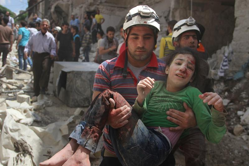 A man carries injured girl after Russian forces staged air-strike over Aleppo's opposition controlled Kellase region, Syria on April 28, 2016.